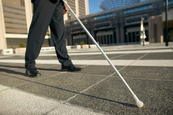 Man walks on pavement with a white cane