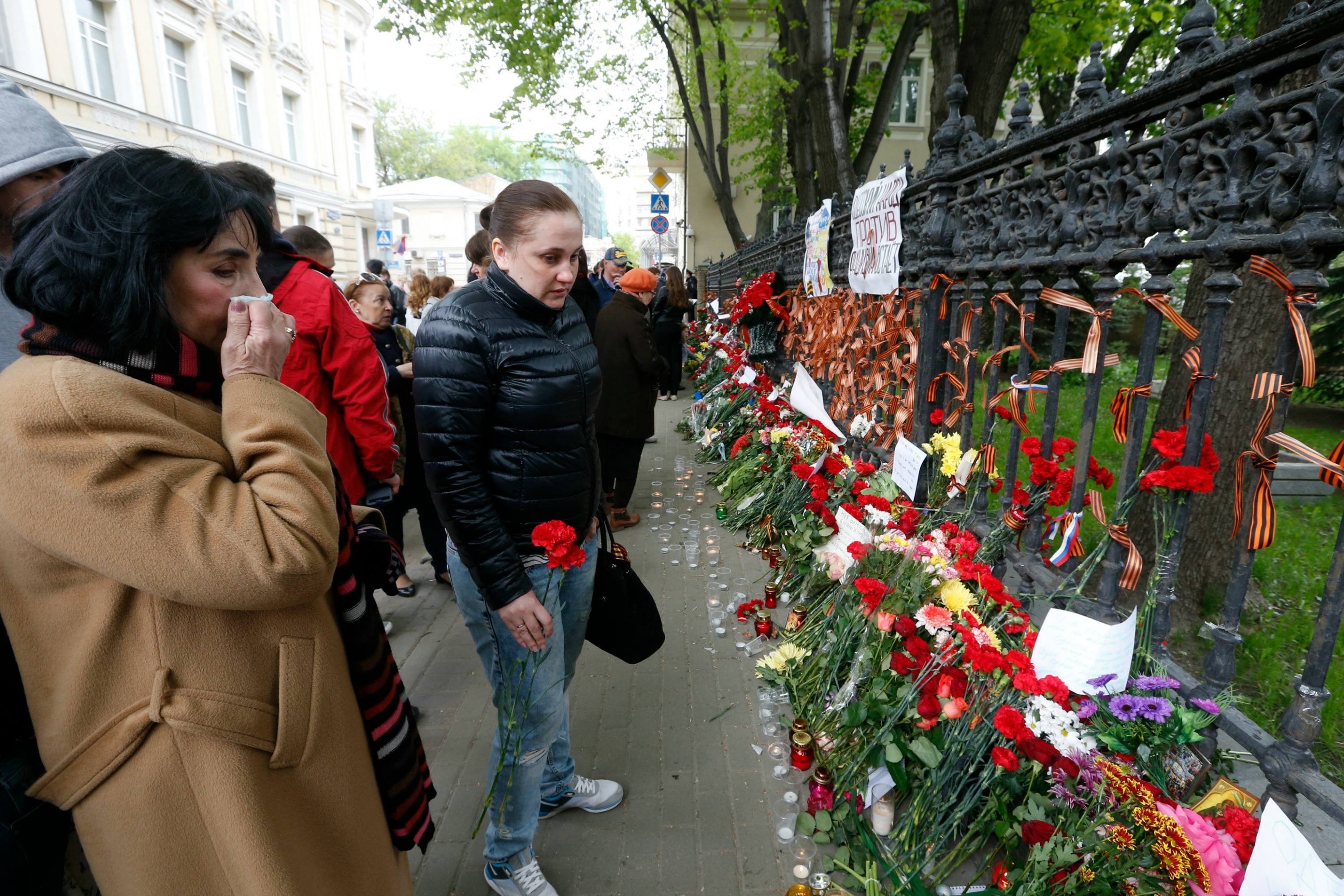 People bring flowers, lit candles and black and orange ribbons of St. George to mourn the death in Odessa, at the gate of the Ukrainian embassy in Moscow. Photo Reuters