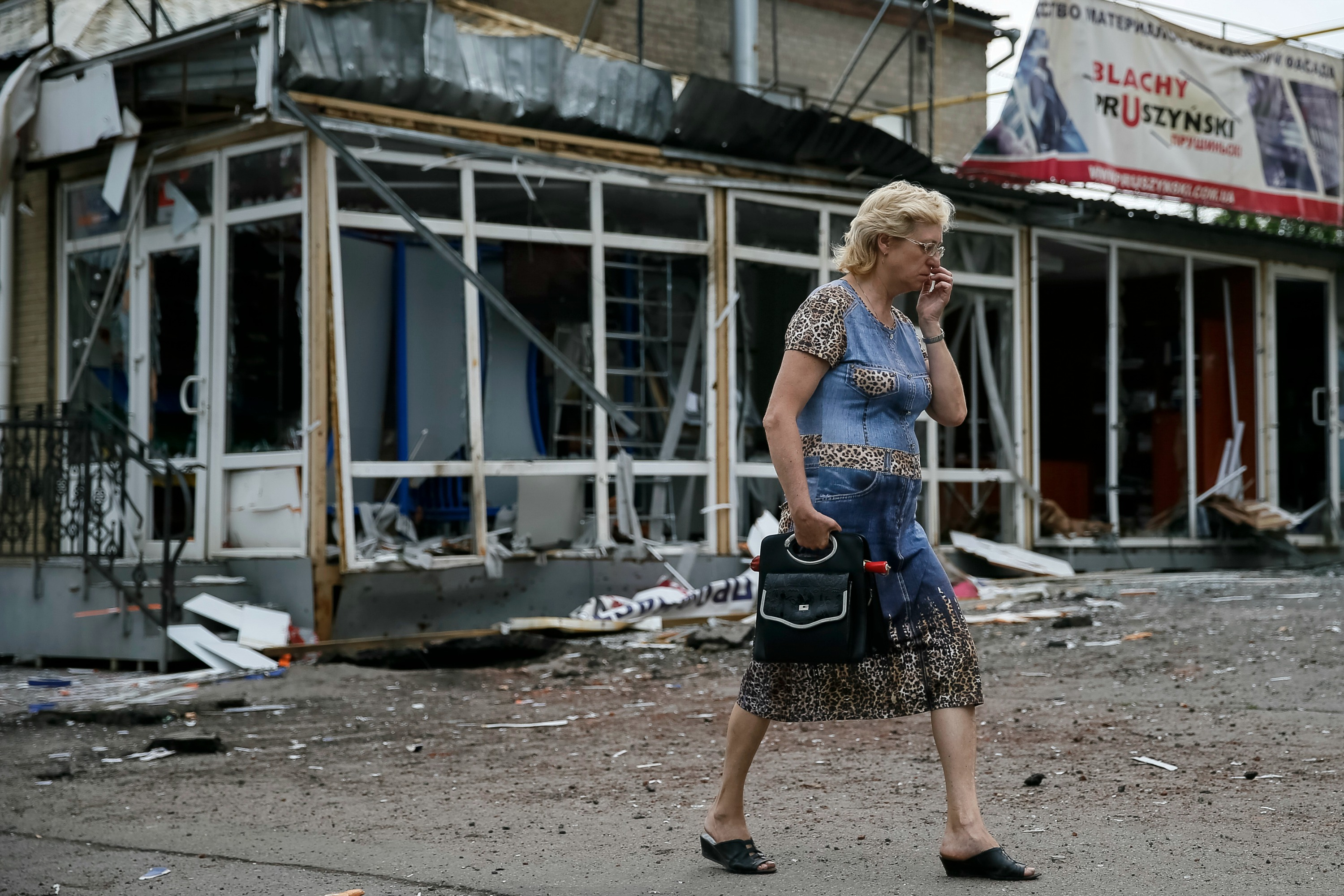A woman passes destroyed house following what locals say was overnight shelling by Ukrainian forces, in Slaviansk, 10 June 2014.