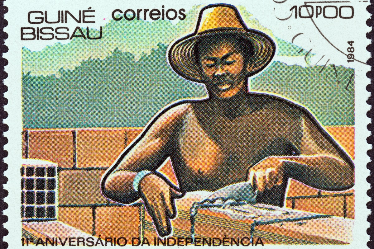 """A stamp printed in Guinea-Bissau from the """"11th anniversary of Independence"""" issue shows laying bricks, circa 1984 [Photo: Shutterstock]"""