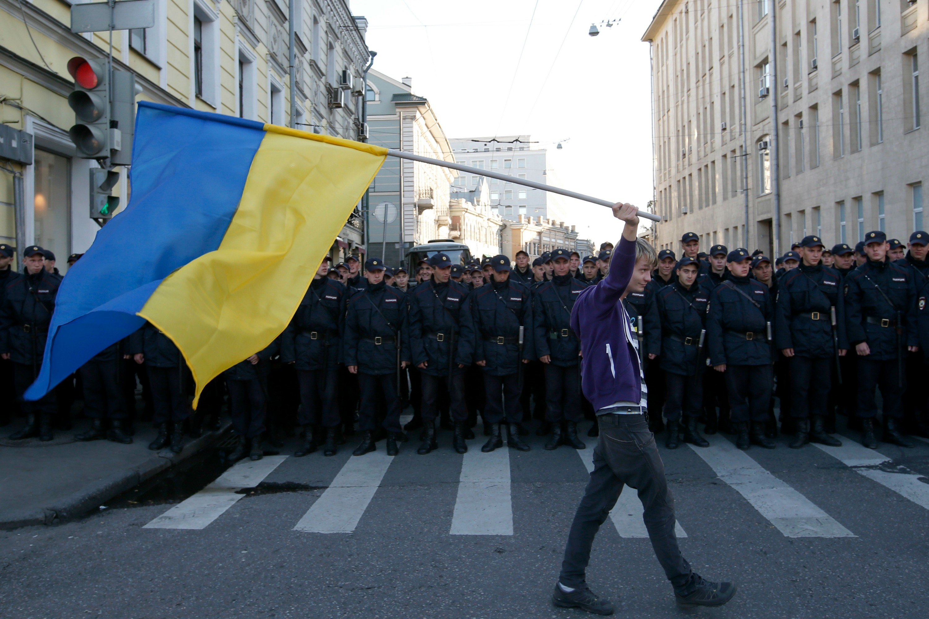 A young man with a Ukraine flag defies the police in Moscow, 21 September [Reuters]