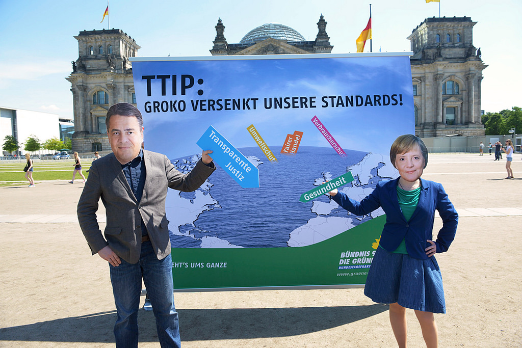 Protesters disguised as Germany's Economic Affairs Minister Sigmar Gabriel and Chancellor Angela Merkel pose in front of the Reichstag building. Berlin 2014 [Bundesfraktion Bündnis 90/Die Grünen / Flickr]