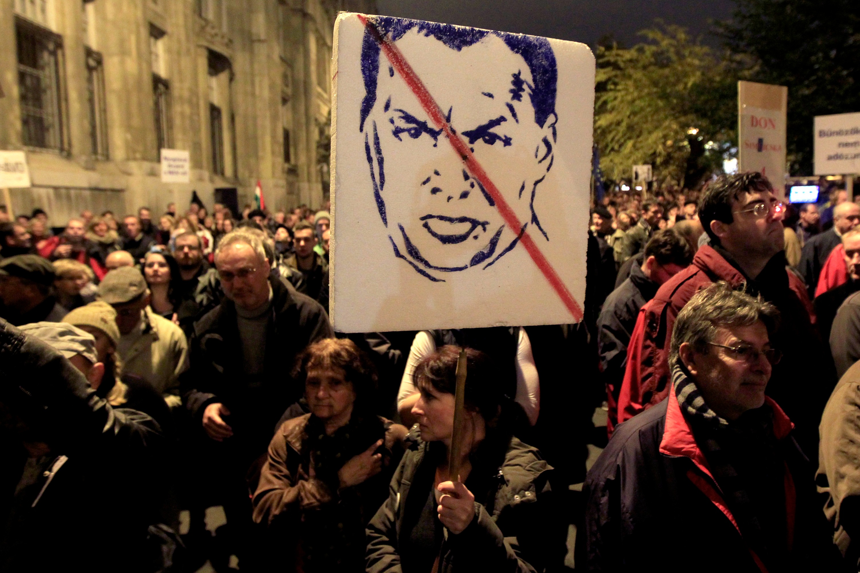 A woman carries a placard with the likeness of Hungary's Prime Minister Viktor Orbán as thousands of Hungarians protest against perceived corruption at the country's tax authority and lack of wider democratic freedoms, in Budapest, 9 November 2014 [Reuter
