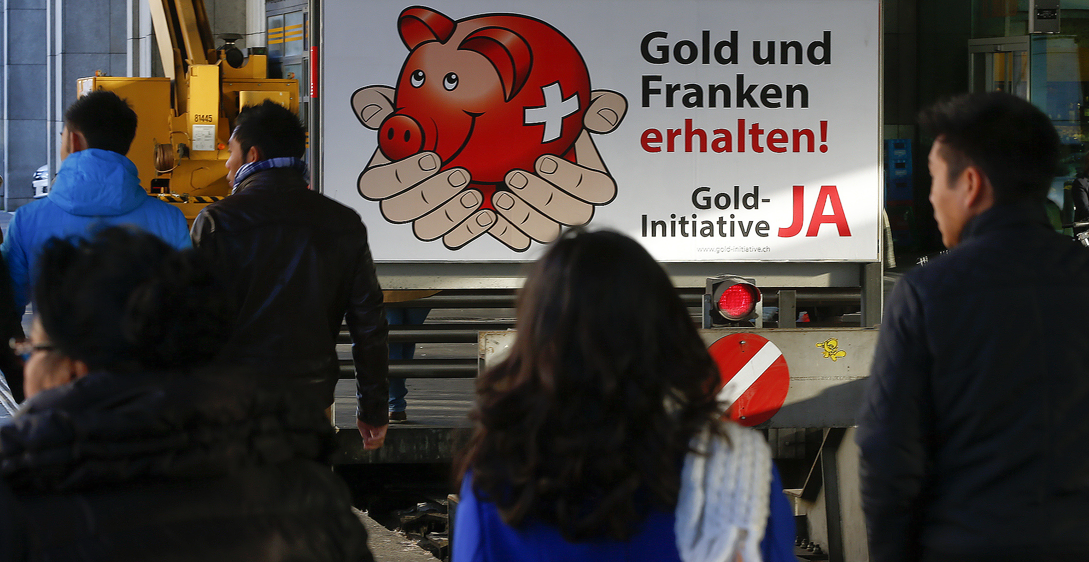 People walk in front of a banner for the gold initiative at the main train station in Zurich [Reuters]