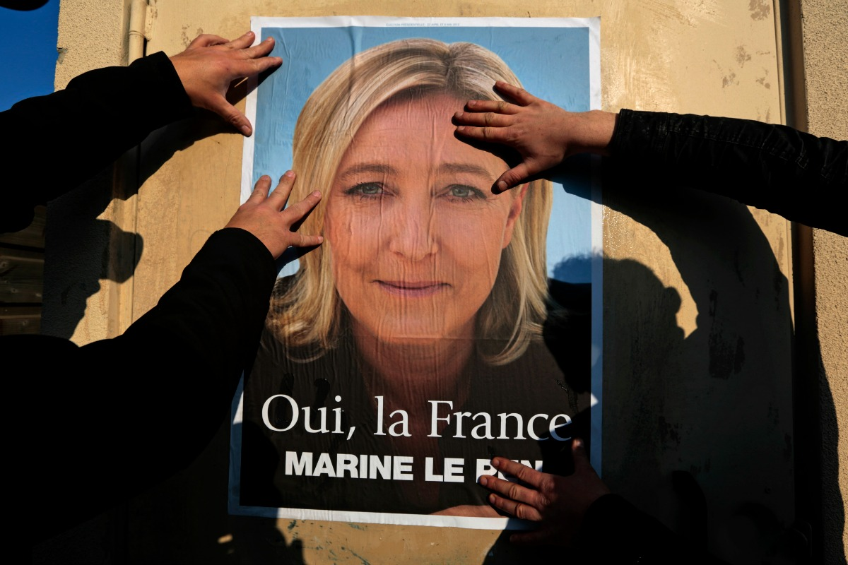 Supporters paste a poster of Marine Le Pen, France's National Front leader, on a wall before a political rally for local elections in Frejus March 18, 2014. [Reuters]