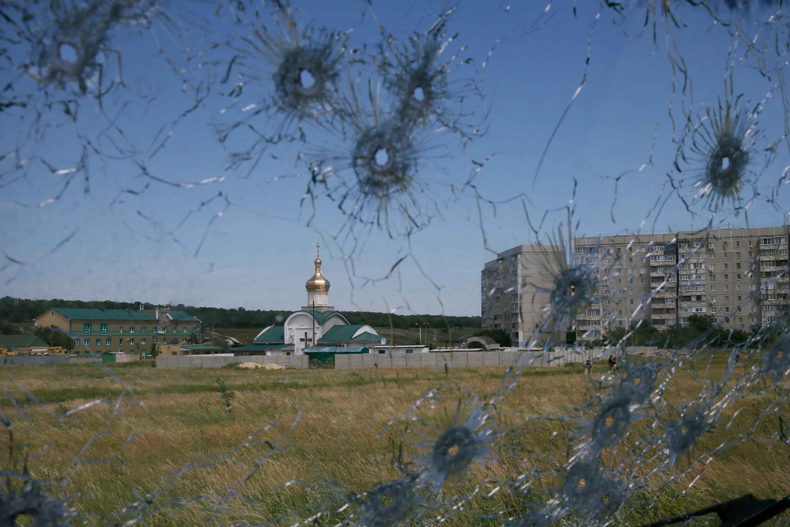 A Ukrainian border post is seen through bullet holes in a truck's windscreen on the outskirts of the eastern Ukrainian city of Luhansk, 3 June. Photo: Reuters