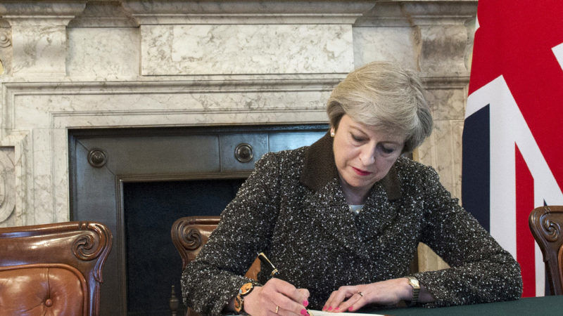 a handout photo made available by 10 downing street on 29 march 2017 shows british prime minister theresa may signing a letter of notification to the